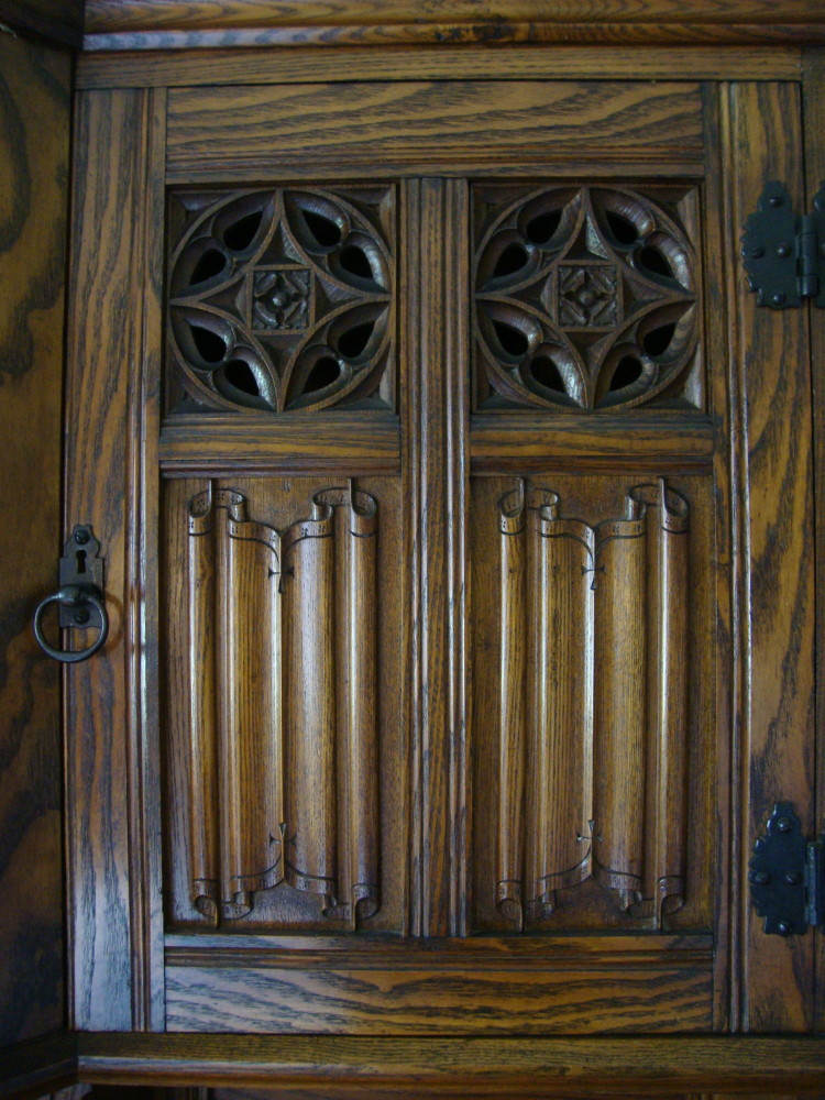 A close-up view of a cabinet door above the fireplace mantle. The star pattern in the thru relief carving shows up in many places in the library.