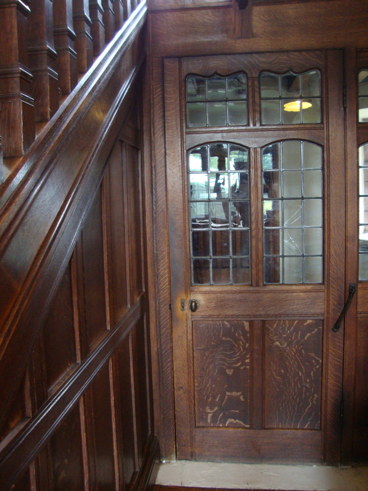A view of a service entrance door next to a stairwell featuring framed paneling.