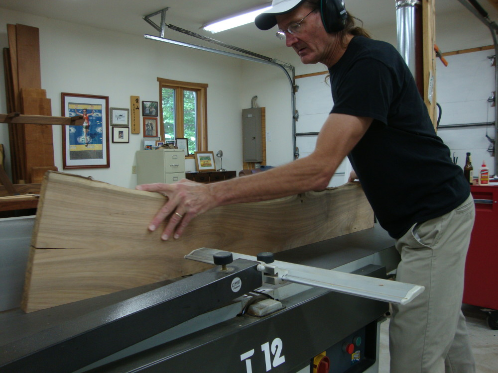 Using the jointer to square up the edge after ripping the slab in two. One light pass over the cutterhead is enough.