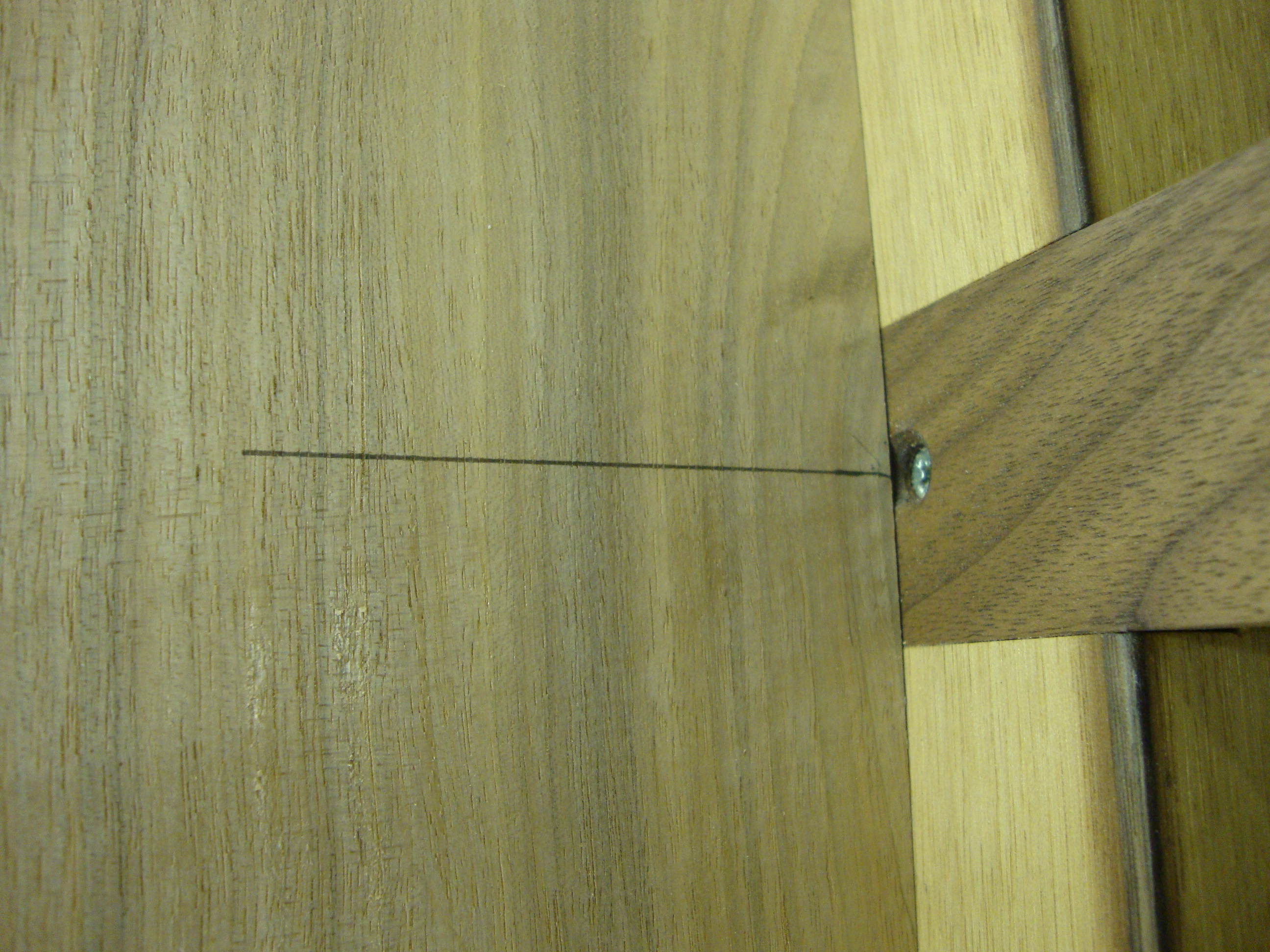 The cut line centered on the support arm on the table base.